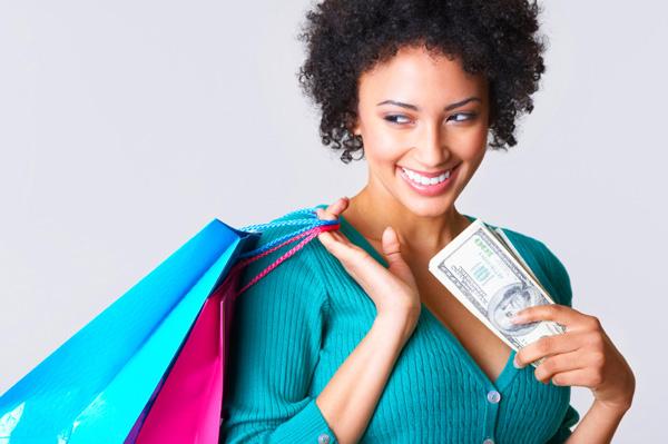 femeie de culoare neagra cu plase de cumparaturi si bani in mana